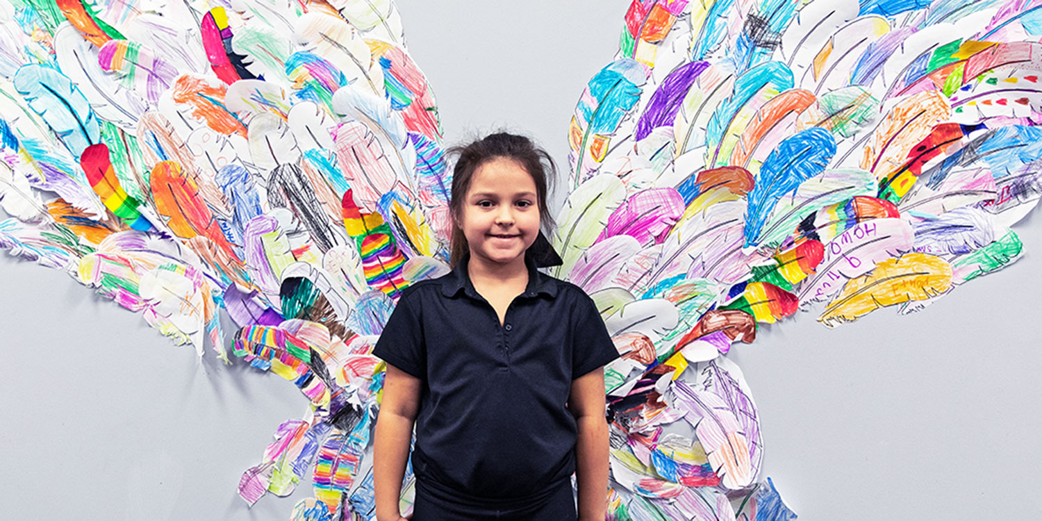 Smiling student standing in front of a feather butterfly wing wall display.