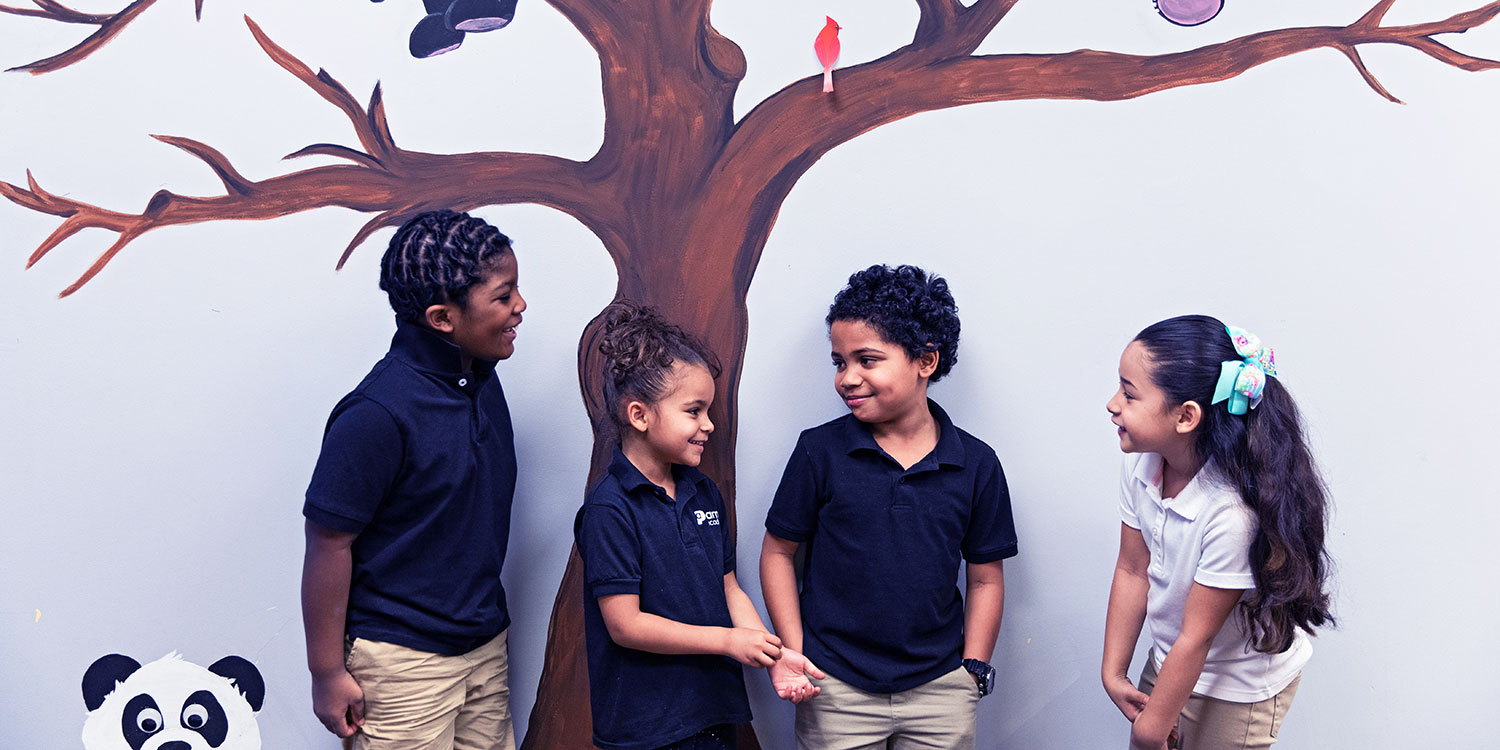 Smiling students standing in front of a wall mural.