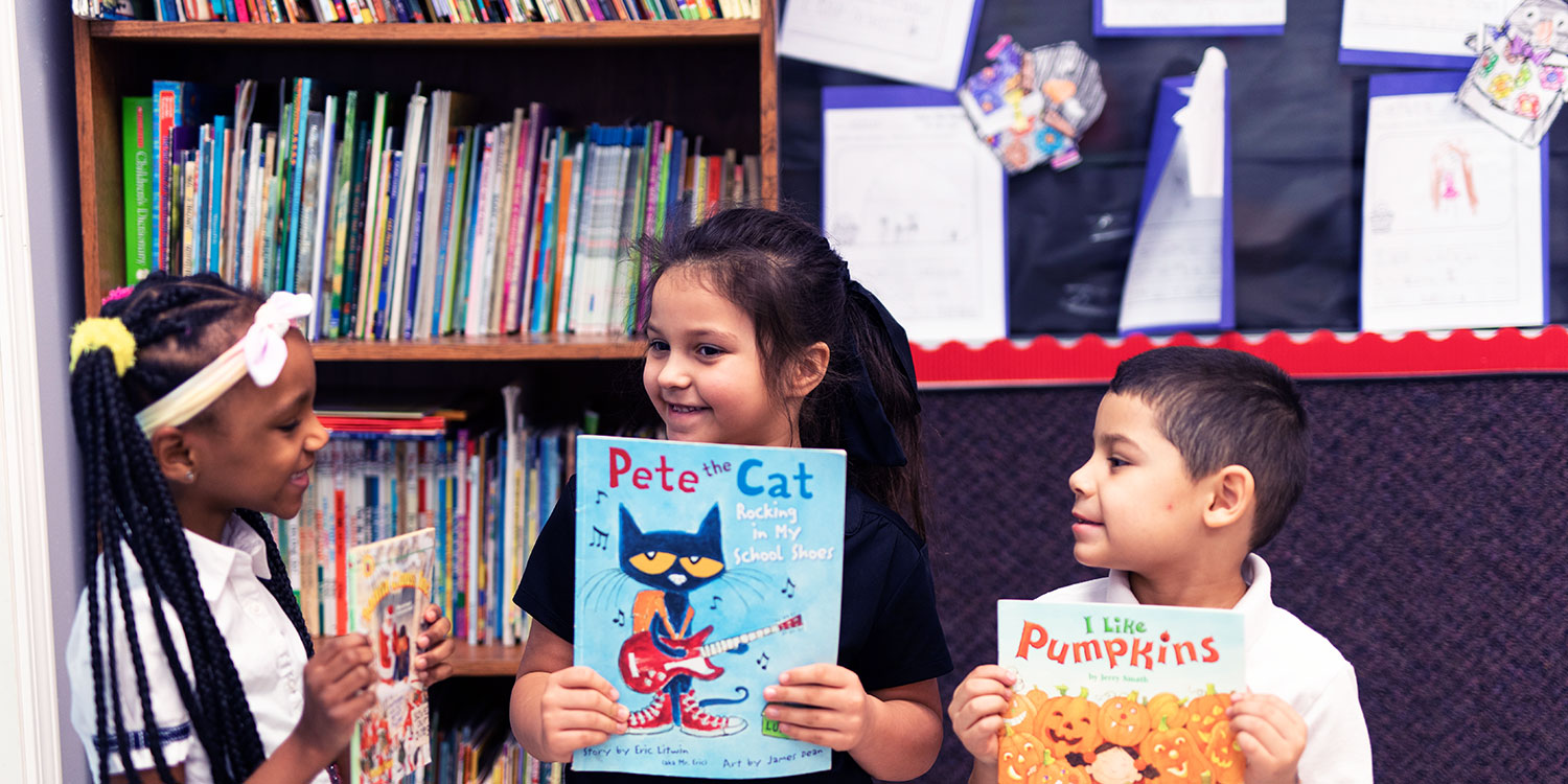 Smiling students holding up books in a classroom.
